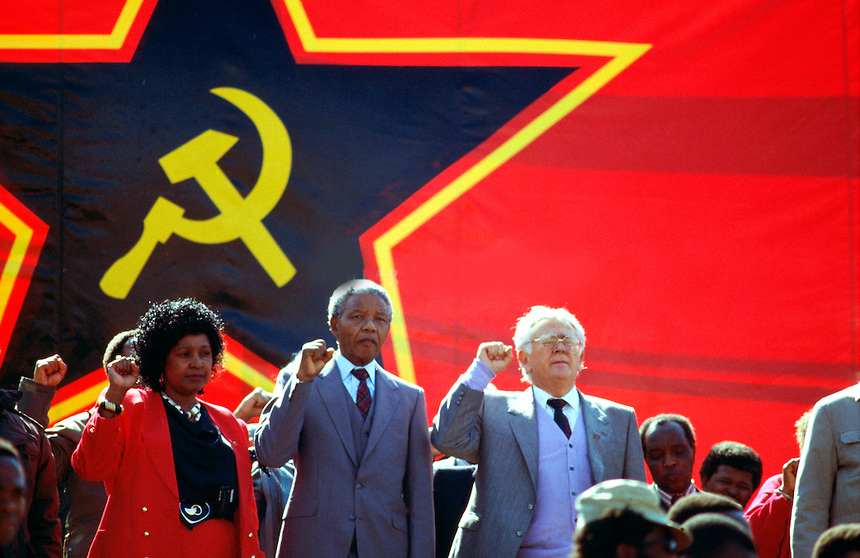 Winnie Mandela, Nelson Mandela and Yossel 'Joe' Slovo at an ANC rally in front of a very large communist flag