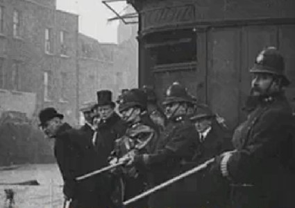 Anarchy in the UK (1909-1911): A young Winston Churchill (in top hat) watching the Siege of Sidney Street